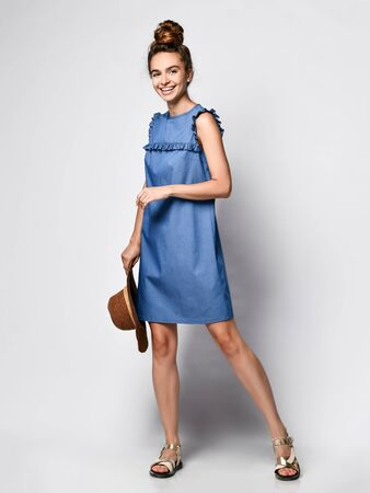 curly female model in a blue urban denim dress in full growth with a straw hat in her hands. Lovely girl in romantic clothes goes on a date, to the office, to a meeting. Urban fashion