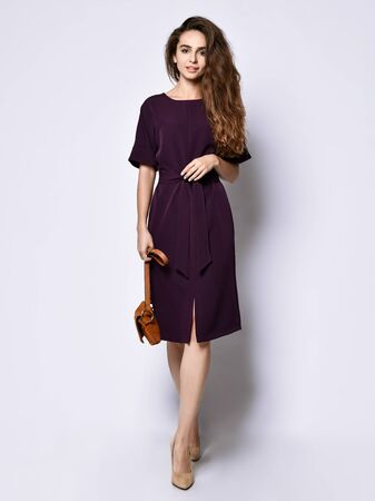 Curly slim female model in a purple dark long dress, with a small purse and high heels is a date for a meeting, smiling pretty isolated on white background.