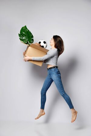 woman is infinitely happy to move to her new dream home. She jumps for joy holding a cardboard box with things - a hat. ball. plant. The concept of relocation. Side view Stockfoto