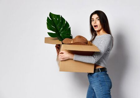 young attractive brunette woman holds a cardboard box full of things - plant, hat and others. She is dressed in jeans and a casual jersey. Concept relocation fees