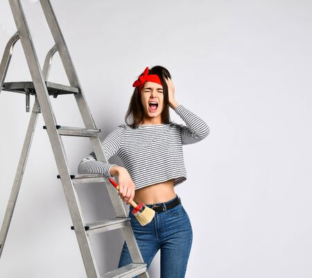 surprised Young brunette girl with a brush and a stepladder - how much work will have to be done on painting the walls. The concept of repair and interior design