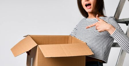 Delivery, relocation and unpacking. Smiling young woman holding cardboard box isolated on white background Stock Photo