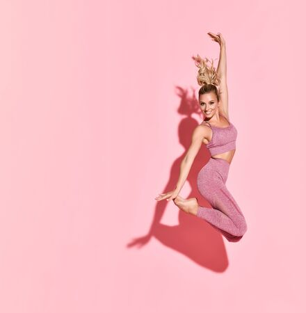 Happy athletic woman jumping in silhouette. Photo of sporty woman in fashionable pink sportswear on pink background. Sport and healthy lifestyle. Dynamic movement. Archivio Fotografico