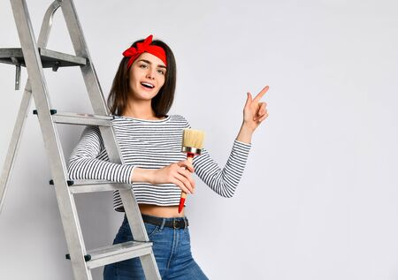 Young brunette girl with a brush and ladder - indicates a space for your advertising. The concept of repair and interior design