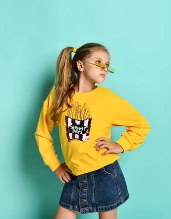Charming fashionable teenage girl in denim skirt and yellow hoodie posing in modern glasses. Fashion childhood