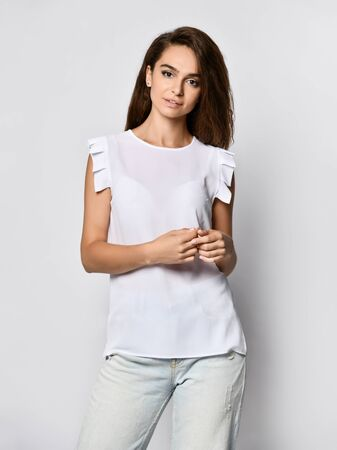 Fashion model wearing ripped boyfriend jeans, white blouse shirt. Fashion urban outfit. Casual everyday clothing style. Stock Photo