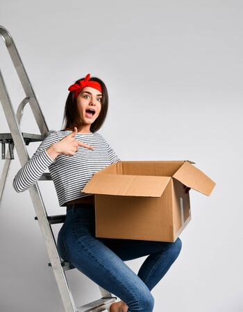 Surprised young woman holding a cardboard box on a light background, sitting on the iron stairs. We are preparing for repair and moving. Delivery and unpacking.