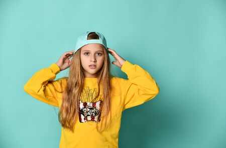 Funny teenage girl in a baseball cap and yellow hoodie covered her ears with her hands on a blue background. 版權商用圖片