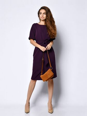 Slim curly female model in a purple dark long dress looking down in full growth. . Cute girl in romantic clothes is going on a date, smiling pretty on a white background.
