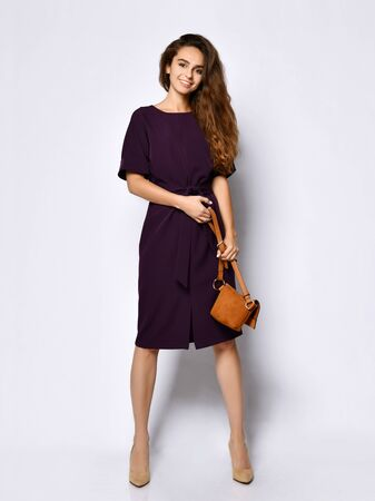 slender curly female model in a purple dark long dress and a small brown leather handbag, in full growth. , Lovely girl in romantic clothes goes on a date