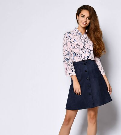 Fashionable woman in a beautiful satin blouse with an ornament and a short blue skirt with buttons smiling at the camera. Fashion spring autumn photo