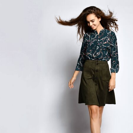 cheerful young woman posing alone, in a dark silk blouse with floral patterns, in a dark short green short skirt with buttons, looks down with a smile.