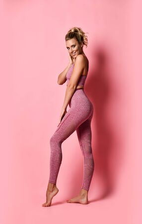 sports woman stands sideways, demonstrating her tightened buttocks, satisfied with the results of fitness training and diet, has a happy facial expression, wears a sports top and leggings, posing on a pink background. Slimming concept