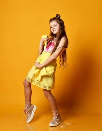 Full length portrait of a cute little teen girl in stylish skirt and jacket clothing knotted at the waist, looking at the camera and smiling against a yellow studio wall. Children's fashion concept