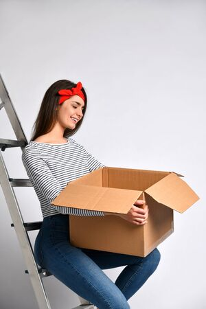 Surprised young woman holding a cardboard box on a light background looking at the contents, sitting on an iron staircase ladder. Getting ready for repair and relocation. Delivery and unpacking.