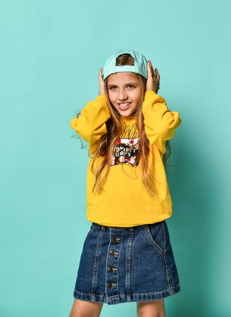 Funny teenage girl in a baseball cap and yellow hoodie covered her ears with her hands on a blue background