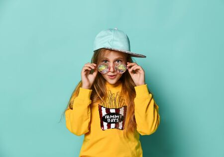Funny teenager girl in a baseball cap, funny trendy casual glasses and yellow hoodie posing on a blue background, looking over fashionable round sunglasses