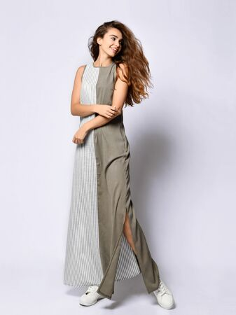 young slender girl with long hair in a long khaki double dress with stripes.