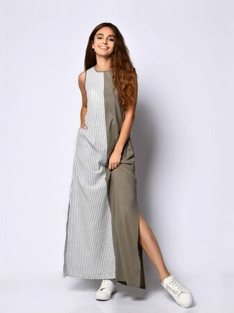 young slender girl with long hair in a long khaki double dress with stripes. Reklamní fotografie