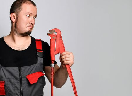 Portraits of a plumber with his red pipe wrench.