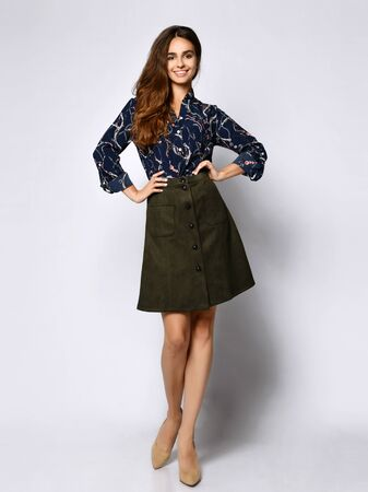 Vertical of a short beautiful cheerful young woman posing in solitude, in a dark silk blouse with floral patterns, a dark short green skirt with buttons and high-heeled shoes, looking with a smile