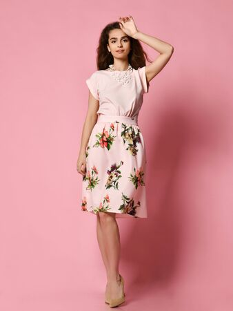 Cute slender girl in a beautiful dress for a date - a blouse and a fluffy flowered skirt posing in the studio on a pink background. to meet spring and summer. Wardrobe update. Stok Fotoğraf