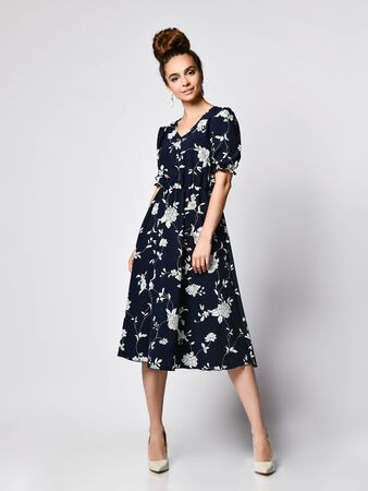 Slim curly female model in a silk pale dark dress looking at the camera in full growth. . Cute girl in romantic clothes is going on a date, smiling pretty on a white background. Stok Fotoğraf