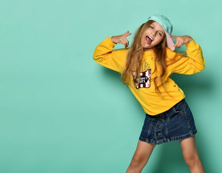 Funny teenager girl in a baseball cap and yellow hoodie is fooling around on a blue background. Having fun showing tongue