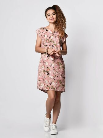 Young cute long-haired woman posing in a new floral pink pattern fashion dress in sneakers happy full body smiles on a white background
