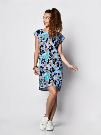 Young cute long-haired woman posing in a new floral blue pattern fashion dress in sneakers happy full body smiles on a white background Stok Fotoğraf