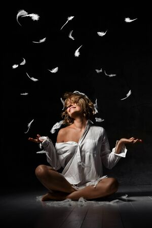 beautiful young blonde is sitting on the floor in one white shirt having fun with feathers. Stormy night. Studio shot. Isolated on blue background