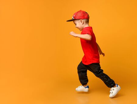 Smiling little boy in a red T-shirt and black sweatpants and a cap runs to the left on a yellow background