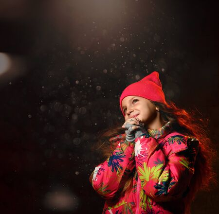 tle girl on a dark background in warm winter clothes, folded her hands in prayer, making a wish, looking up, on a dark background. Bokeh on background
