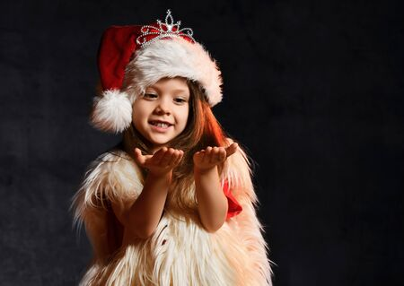 Little cute girl in a santa hat and white fur vest, catches snowflakes on a dark background.