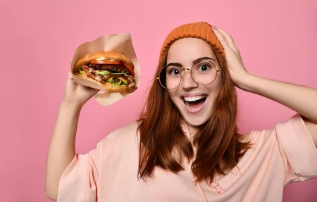 Funny girl with red hair and a hat holding a burger and is surprised at the serving size. Ginger female student has fast food lunch