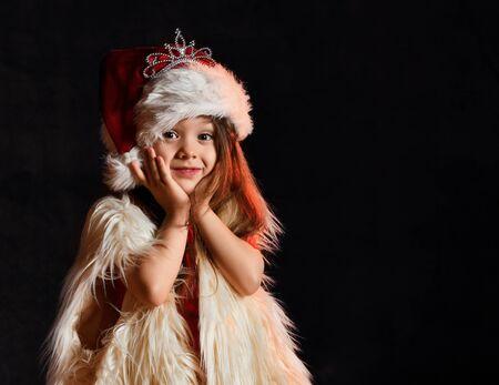 Little girl in santa hat and fur yolk posing on a dark background. Little kid with santa look.