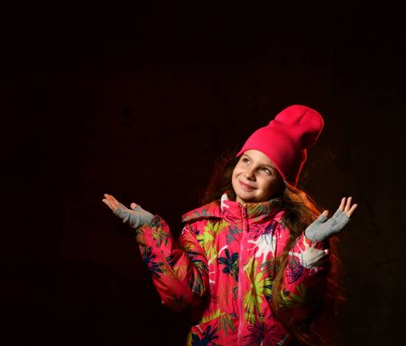 Young beautiful happy little girl on a dark background. The model looks up, wearing a stylish winter jacket, hat, gloves. Urban lifestyle. Empty copy space for text. Stockfoto