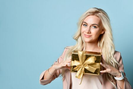 Beautiful elegant young blonde in a beige suit holding a golden gift box. New year photo, birthday presents