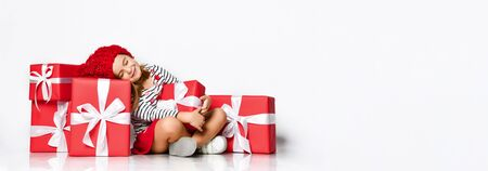 Portrait of a joyful cute little girl sitting in a pile of gift boxes, dreams closing her eyes about something. on a light isolated background, place for advertisement, banner