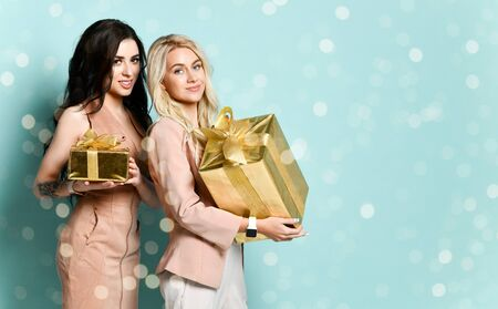 Image of emotional happy young friends women standing isolated over green bokeh background holding gift boxes surprise.