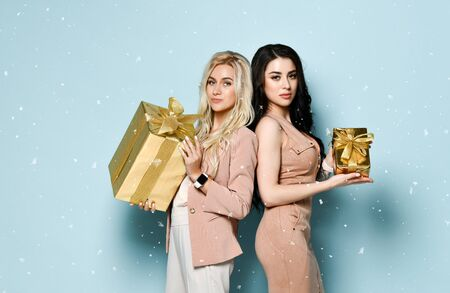Two cheerful brunette and blonde woman in festive beige clothes standing back to back and holding gift boxes, looking at camera, isolated on blue background.