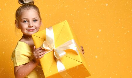 Beautiful cheerful happy child girl with gift box on yellow background Stockfoto
