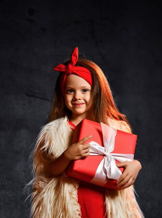 Cute attractive girl in a fur vest and red hairband holds a gift Stockfoto - 134275386