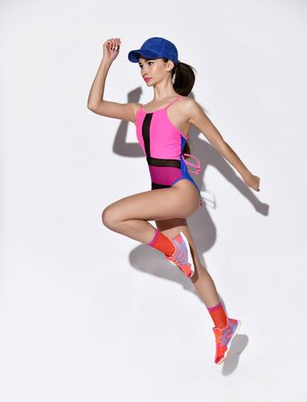 Happy athletic woman jumping on a light background. Photo of sporty woman in fashionable colored sportswear bodysuit and cap. Dynamic movement. Sport and healthy lifestyle