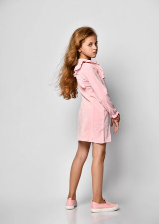 Beautiful little girl with long blond hair and blue eyes, standing on a white background, wearing a pink casual dress and gym shoes, teenager style. Sale, holidays, birthday party concept. Stockfoto