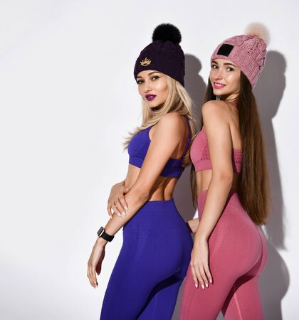 Sporty women, body image of a fit woman wearing a sports bra and leggings, knitted helmets, showing pumped buttocks isolated on a light wall. Diet, fitness and healthy lifestyle concept.