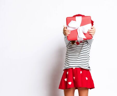 Baby girl hid behind a gift box in a red skirt, on a light background Stockfoto