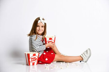 Little cute girl sitting on the floor with two buckets of popcorn and looking at the camera on a light isolated background