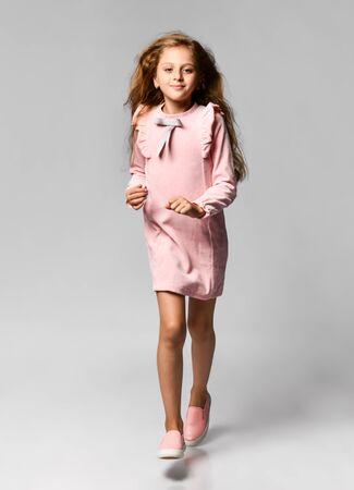 beautiful little girl with long blond hair and blue eyes in a casual pink dress and gym shoes runs to meet you. teenager style. Sale, holidays, birthday concept. Stockfoto - 134275402