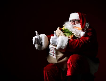 Cheerful Santa Claus is holding a big bag full of fruits and vegetables. Shows class healthy big thumb of the right hand. Enjoy a healthy Christmas dinner. Healthy Christmas Recipes. Christmas diet. Stockfoto
